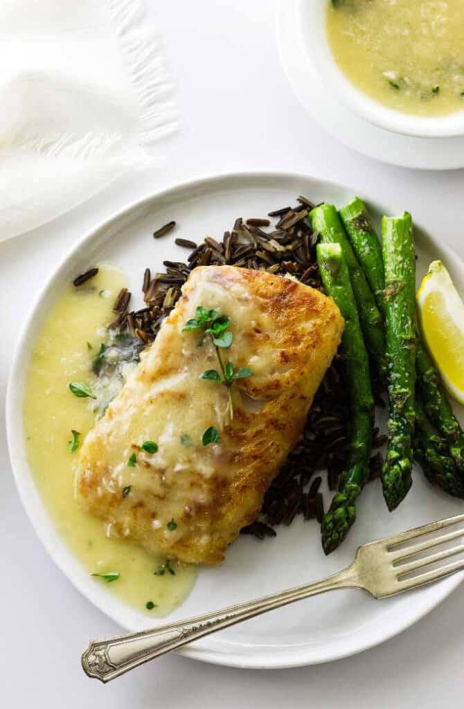 Overhead view of plated cod fillet with lemon-garlic sauce, wild rice and asparagus