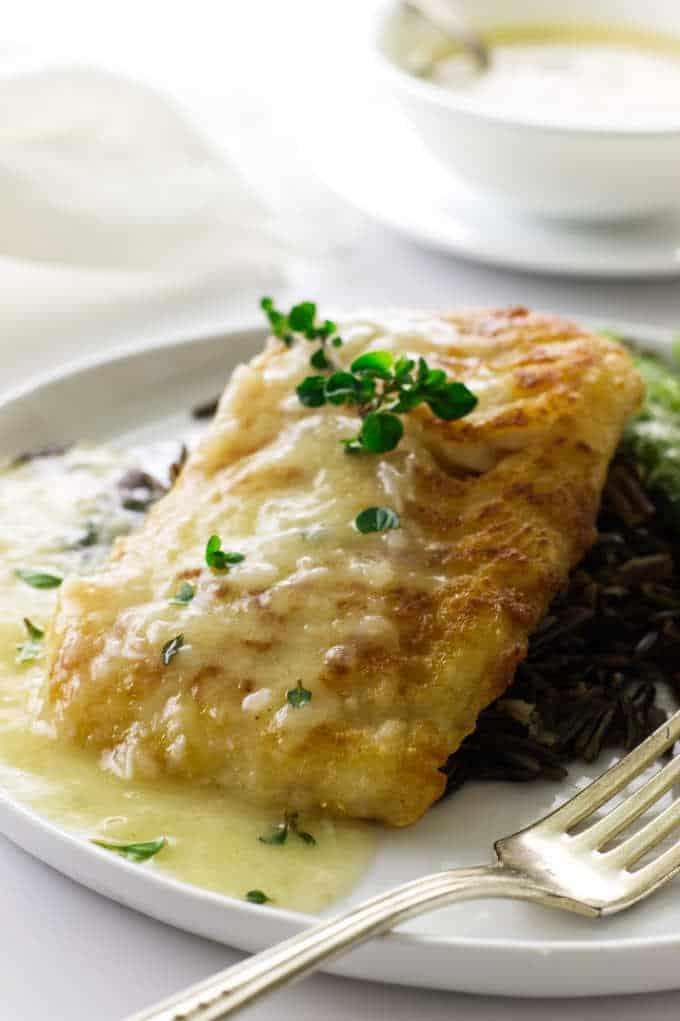 close up view of cod fillet, lemon-garlic sauce, wild rice