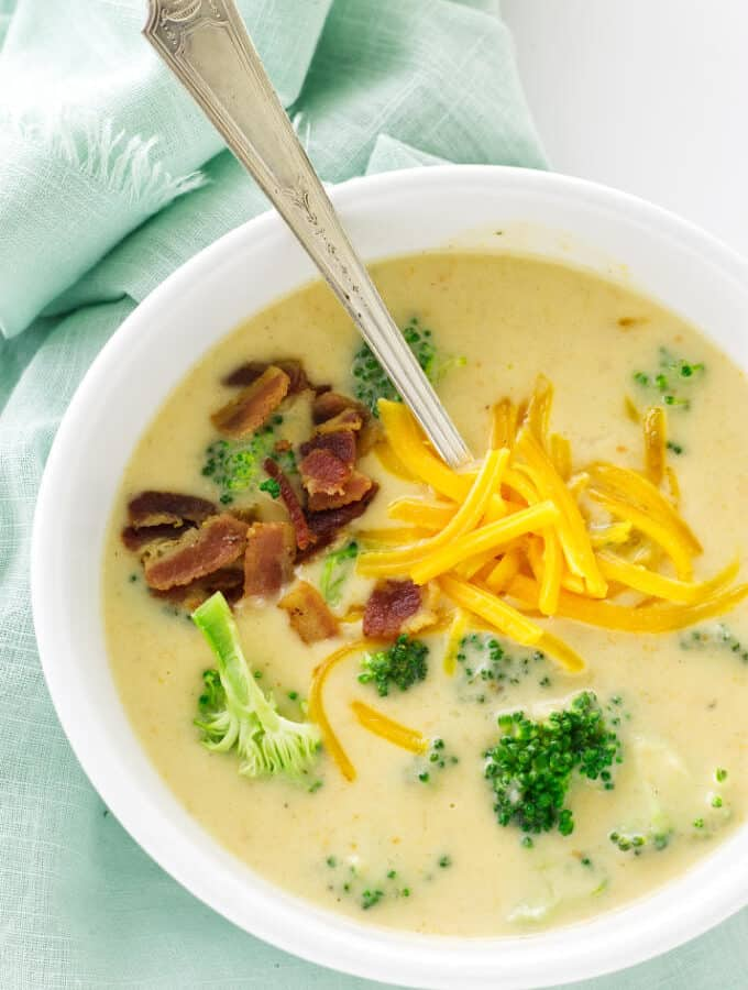 Overhead view of soup, garnished with broccoli, bacon and cheddar