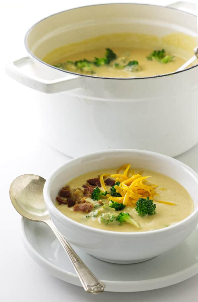 Pot of soup with ladle, bowl of soup garnished with bacon, cheddar and broccoli