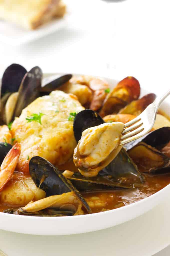 Serving of seafood in romesco sauce with a mussel on a fork