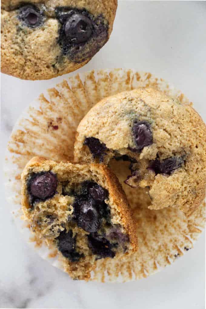 Muffin broke in half showing blueberries inside.