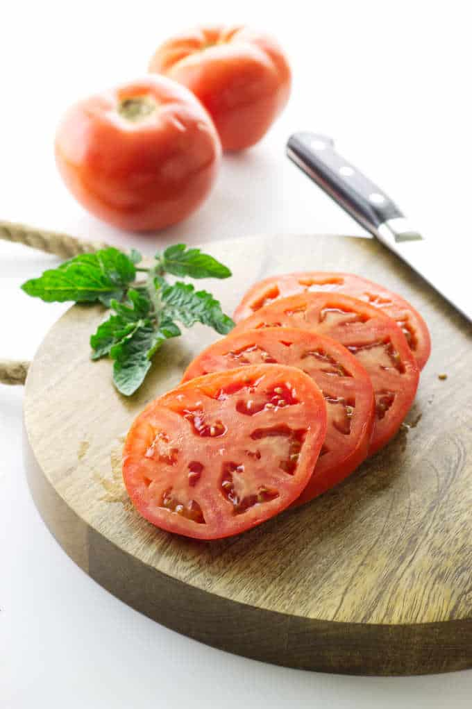 Slices of fresh tomato on a cutting board.