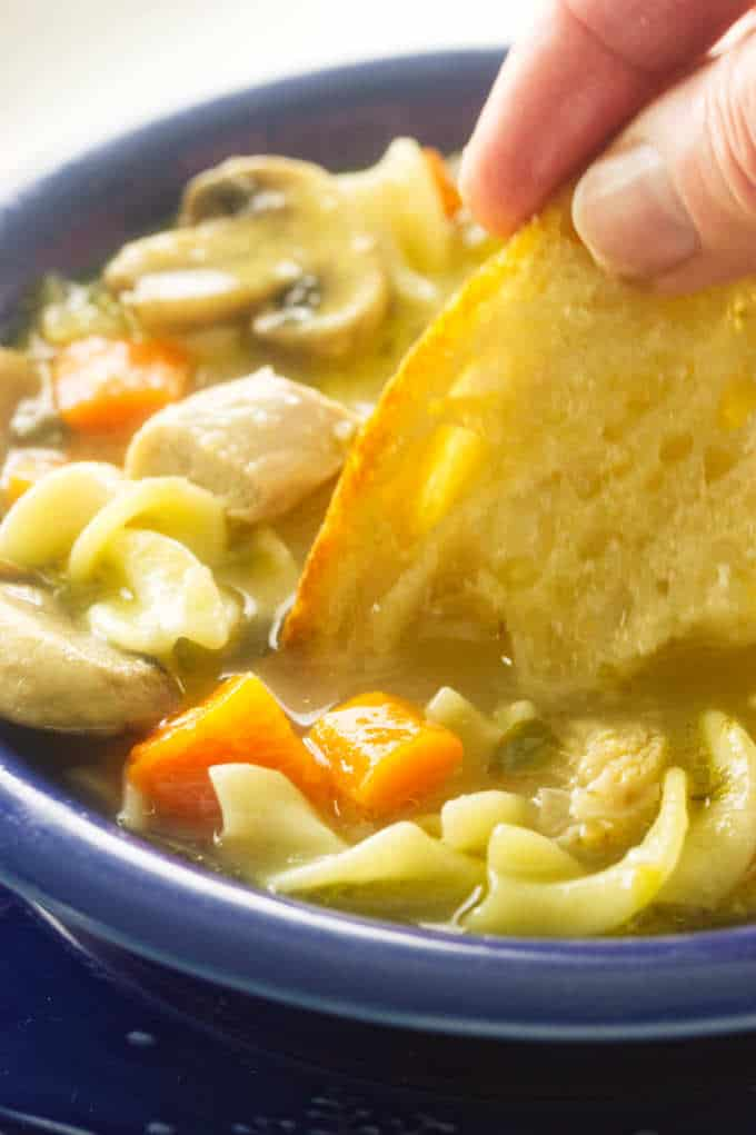 close up view of turkey noodle soup with bread dipped into soup