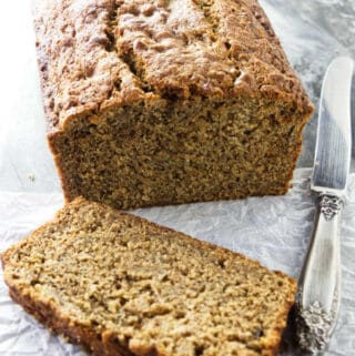 A freshly baked loaf of spelt banana bread with a knife at the side.