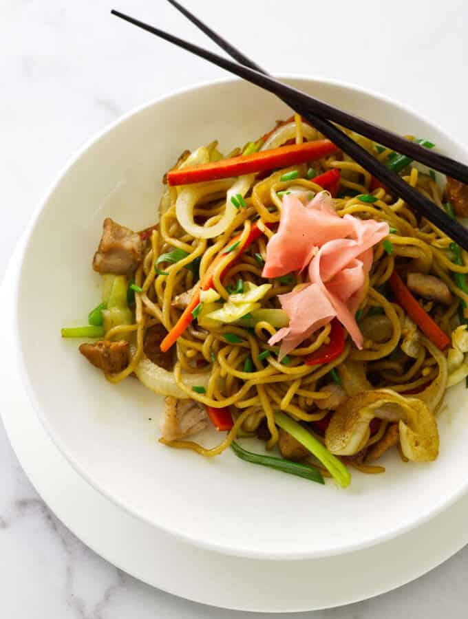 Overhead view of a serving of pork yakisoba with chopsticks