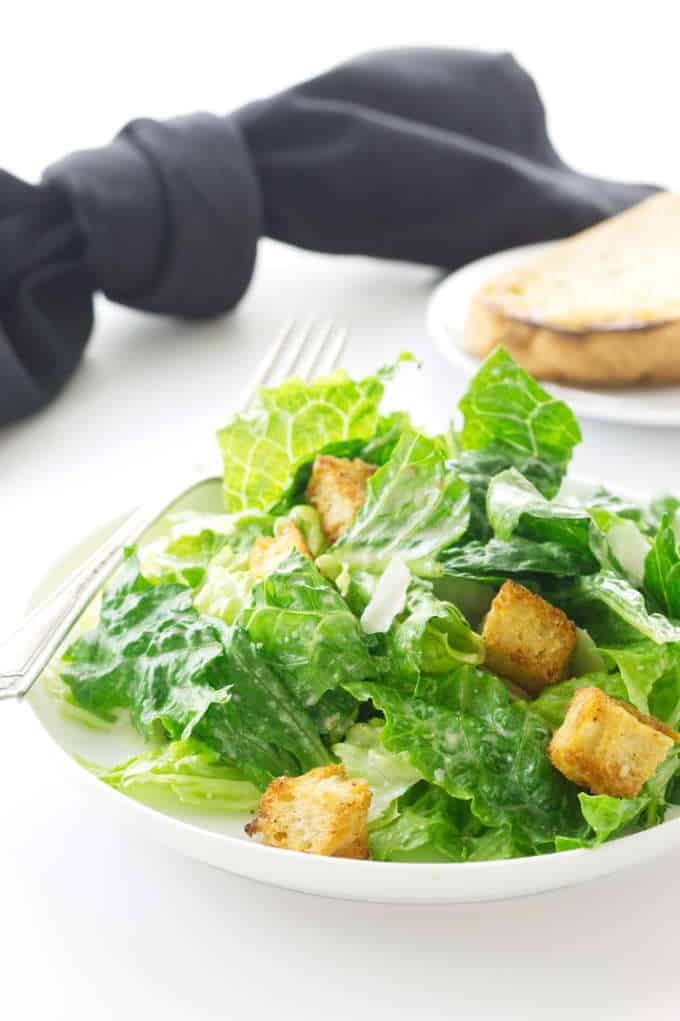 Serving of Caesar Salad on a plate with fork. Saucer with bread in background with black napkin h
