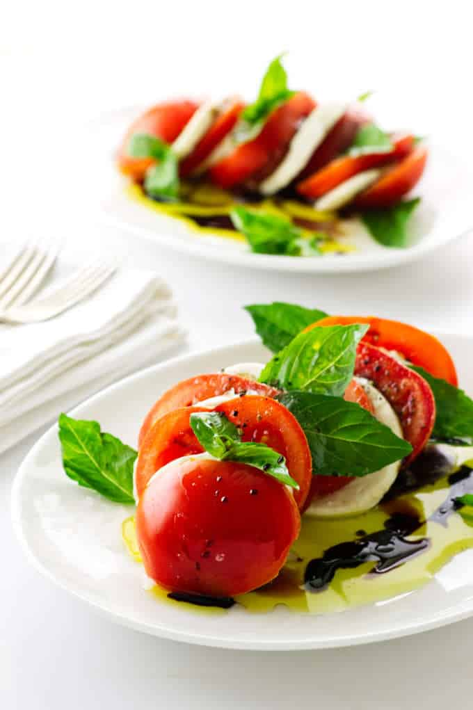 Photo of two servings of tomato, mozzarella and basil salad with oil/vinegar dressing
