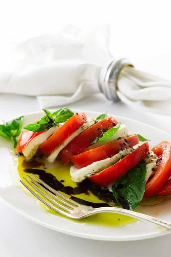 Caprese salad on a plate with fork, napkin in backround