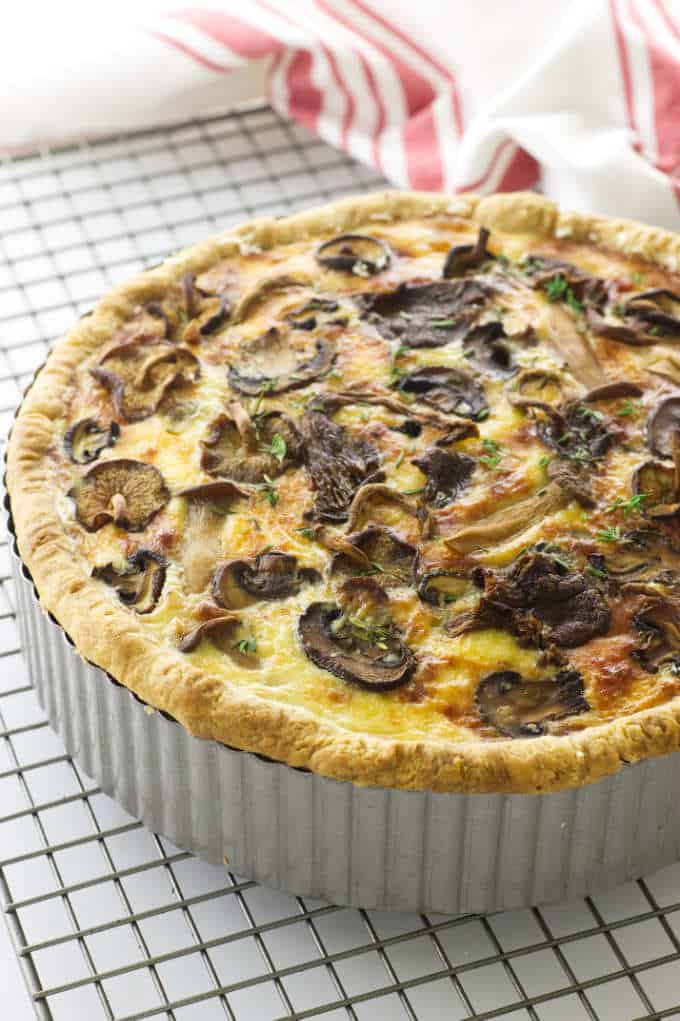 Overhead view of mushroom and goat cheese quiche on cooling rack, towel in background