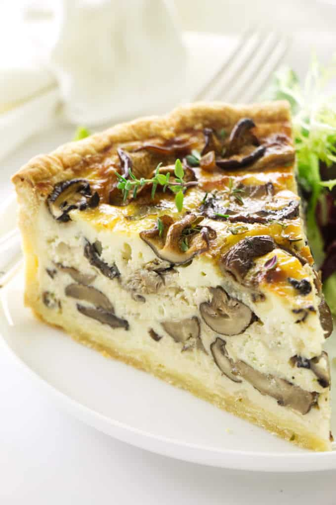 Close up view of a slice of quiche on a plate with a fork, napkin in the background