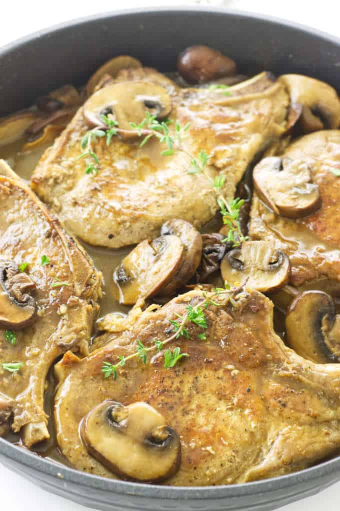 Close up of pork chops and mushrooms in a skillet