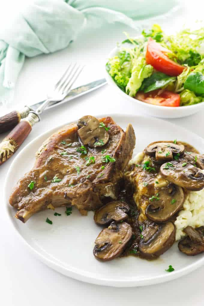 Overhead view of pork chop, mushrooms, mashed potatoes. Salad, fork/knife and napkin
