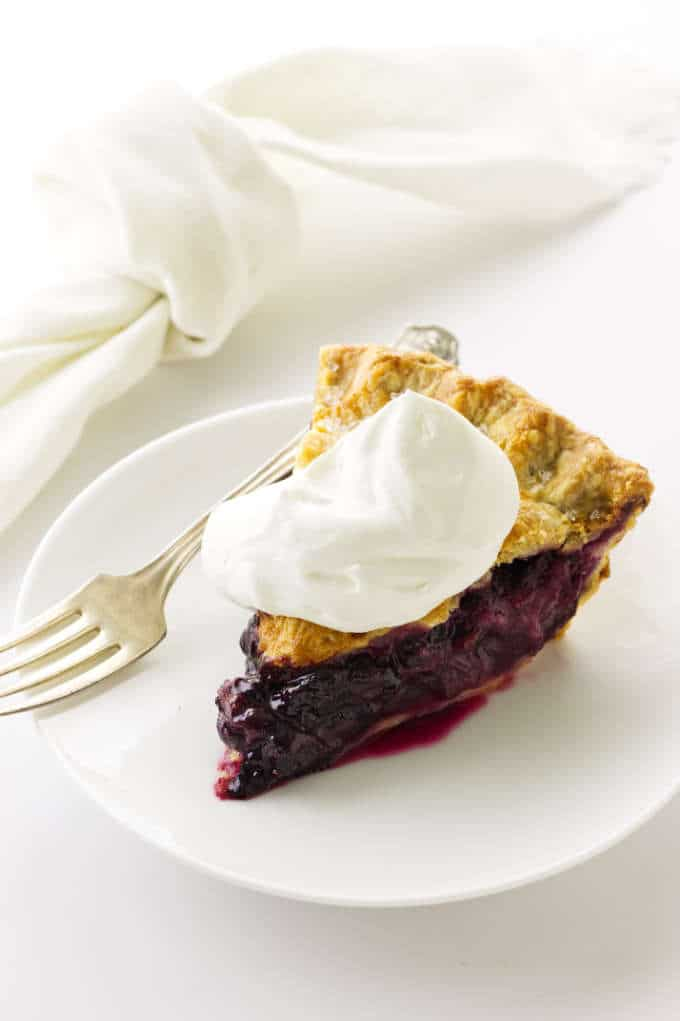 overhead view of slice of pie, whipped cream on a plate with fork. Napkin in background