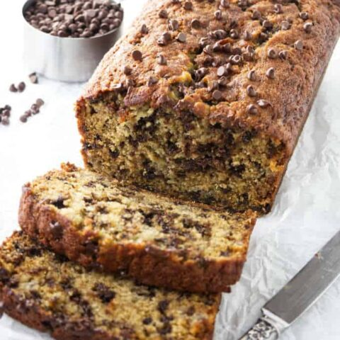 Slices of chocolate chip banana bread next to a loaf of banana bread.