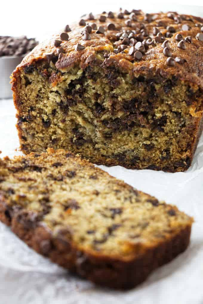 A loaf of chocolate chip banana bread with a slice on the side.