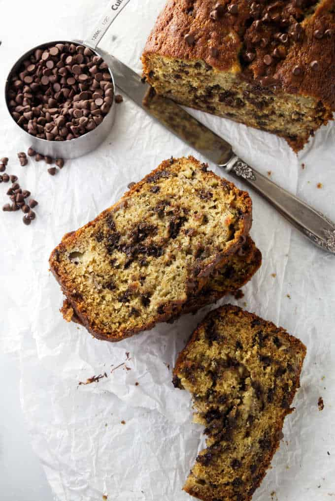 Two slices of banana bread and a cup of chocolate chips.