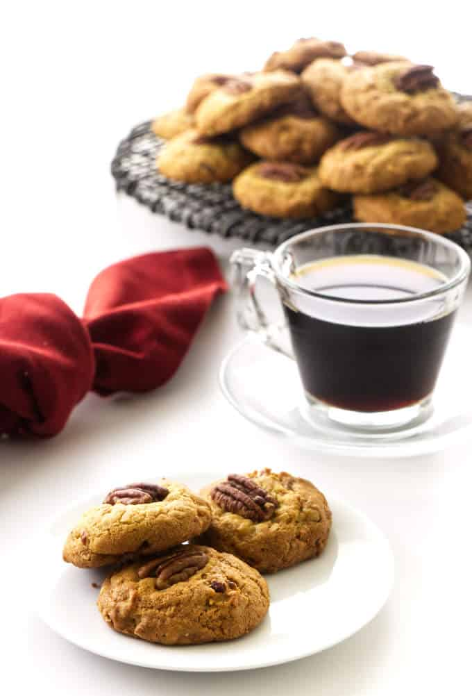 Three cookies on a plate, coffee, cup/saucer, red napkin and stack of cookies