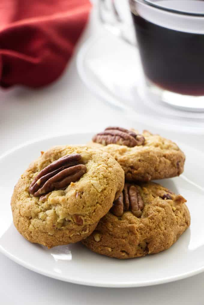 Close up of three coconut pecan cookies, coffee and napkin in background