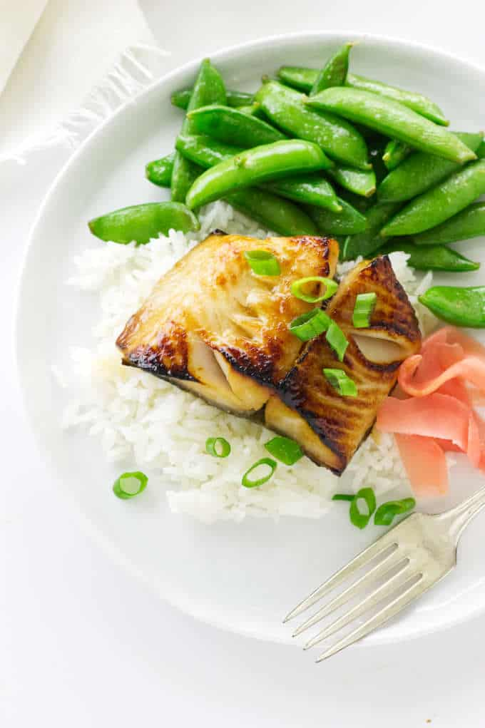 Overhead view of a serving of miso teriyaki sablefish, rice, pickled ginger and snap peas