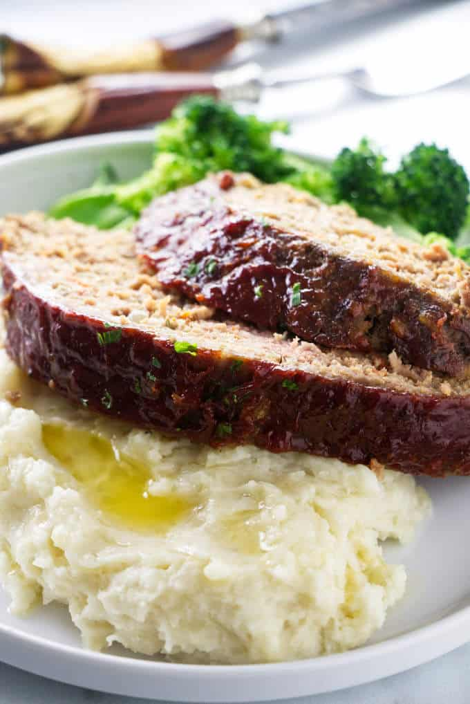 Slices of meatloaf on a plate with broccoli and potatoes.