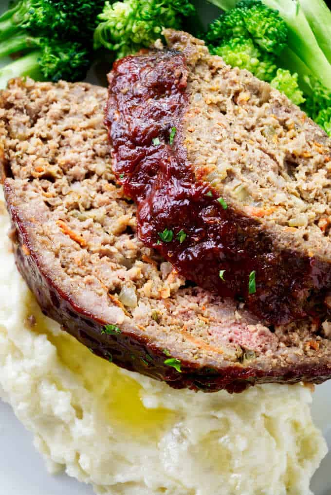 Two slices of pork and beef meatloaf on a pile of mashed potatoes.