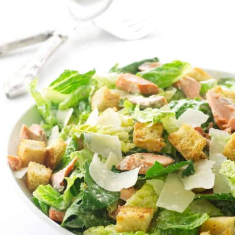 Large bowl filled with salad, serving utensils in background