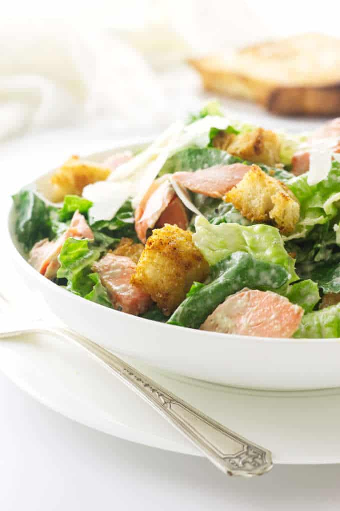 close up view of a serving of salad on a plate with fork. Napkin and garlic bread in background