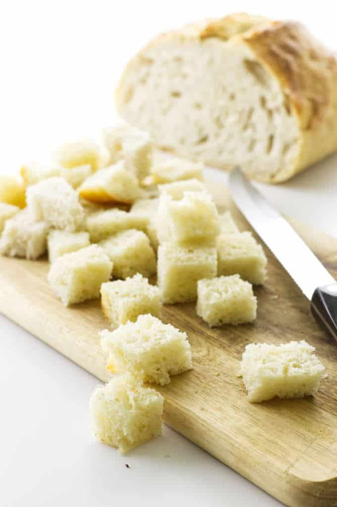 Sourdough bread cut into cubes on cutting board with knife
