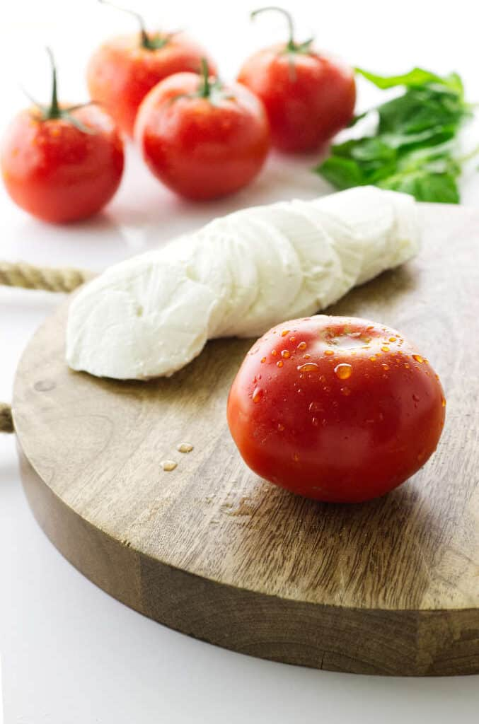 Cutting board with tomato and sliced mozzarella, tomatoes and basil in background