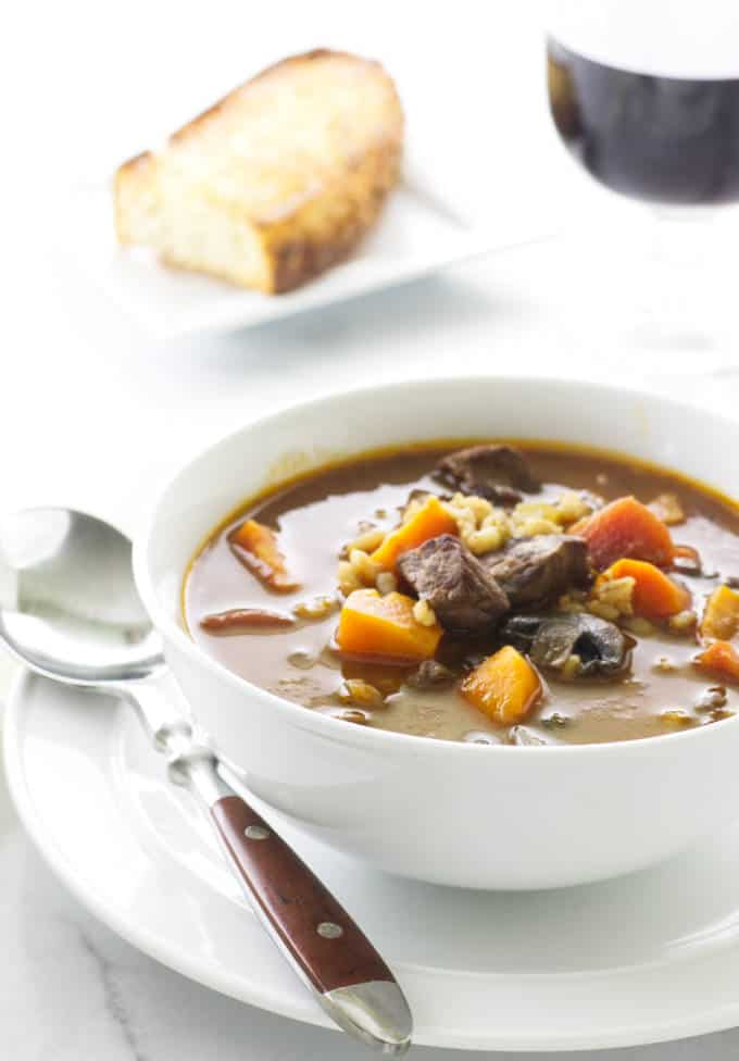 A serving of beef barley soup with a glass of wine and a slice of bread.