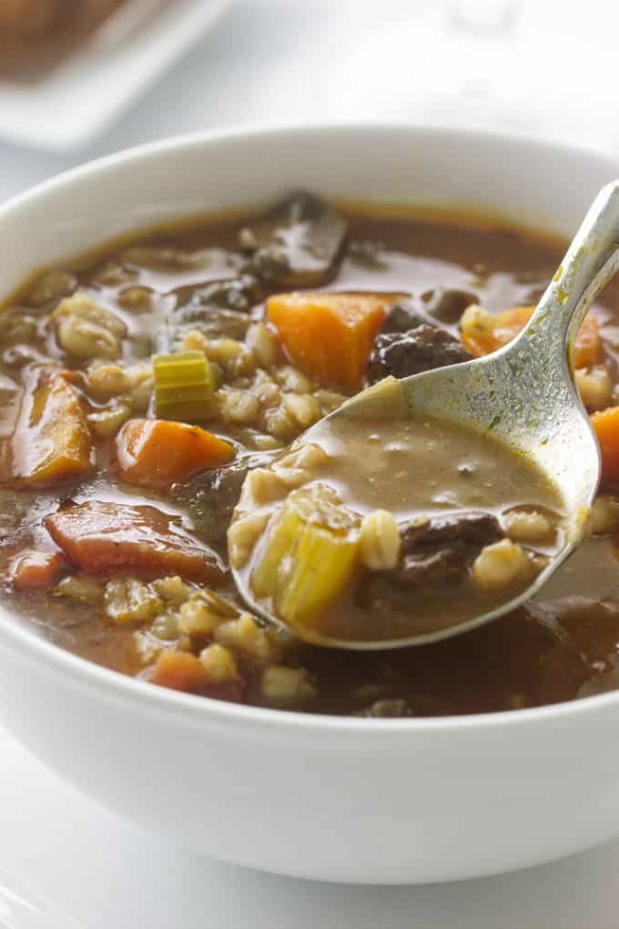 A spoon in a bowl of beef barley soup.