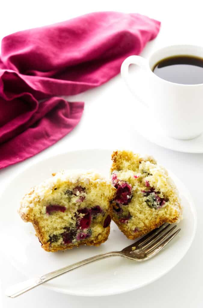 Overhead view of a cranberry muffin on a serving plate with a fork. Napkin and coffee in background