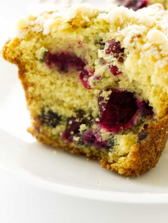 Close up photo of half of a cranberry muffin with walnut streusel topping