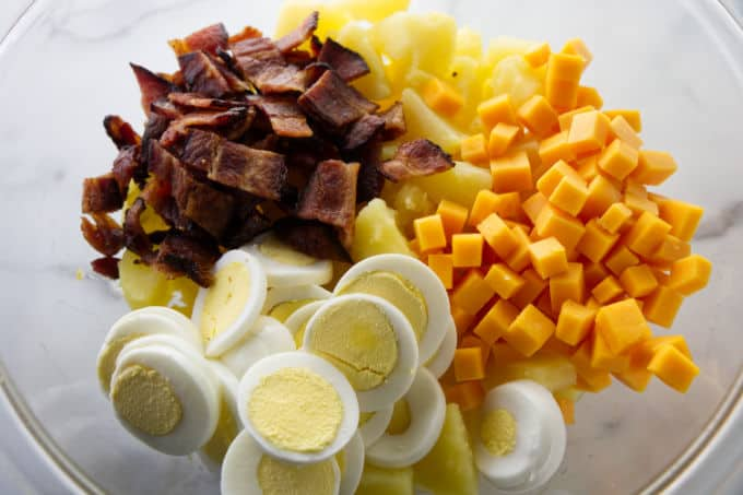 Ingredients for potato salad in a mixing bowl.
