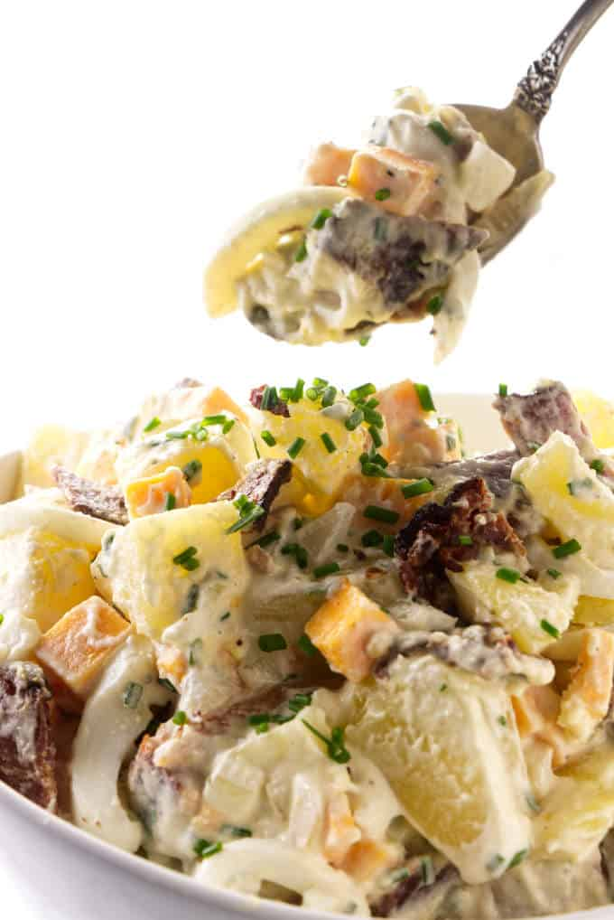 A spoon scooping a serving of potato salad with bacon and eggs.
