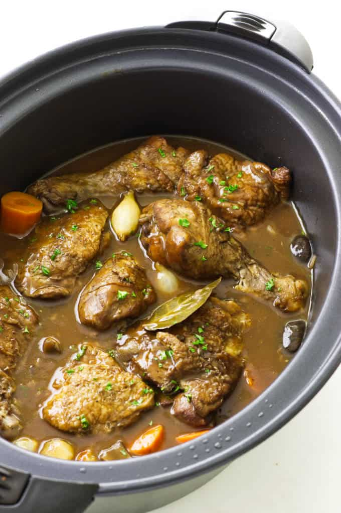 Coq au Vin in an oval slow cooker.