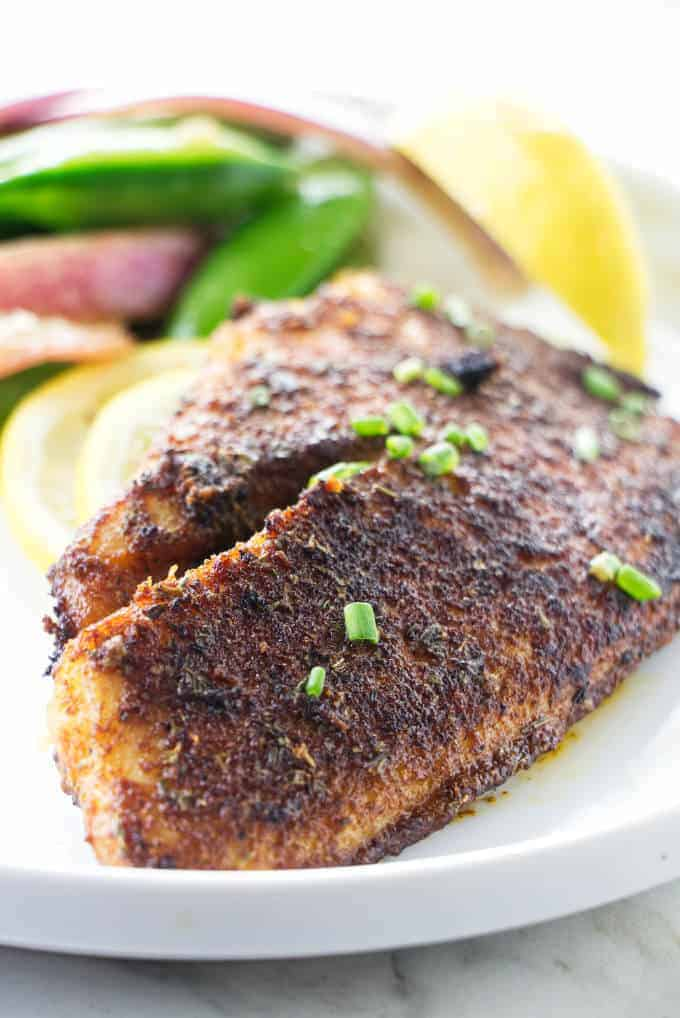 A fillet of blackened tilapia on a plate.