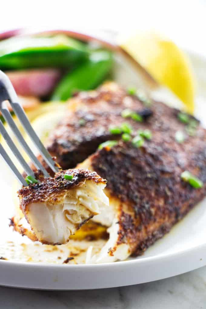 A bite of blackened tilapia on a fork.