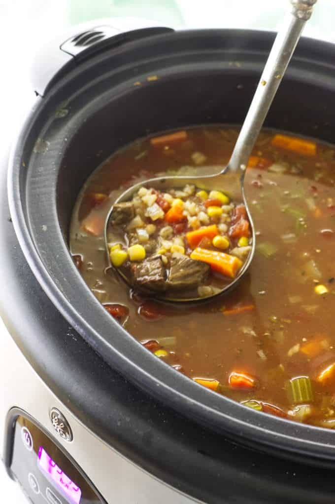 Soup in a slow cooker with a ladle of soup