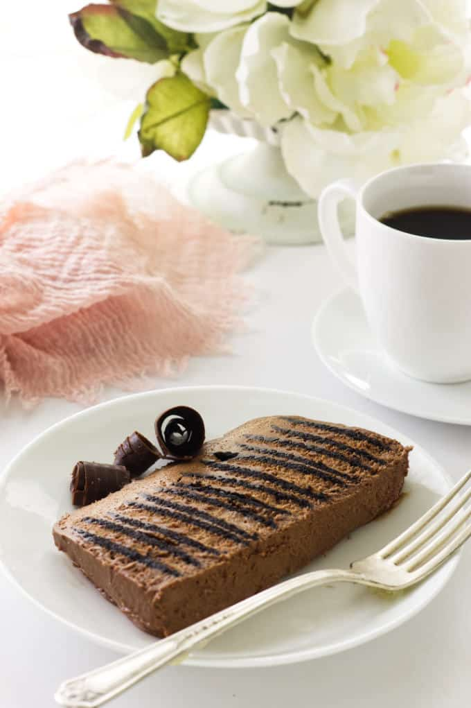 Close up view of a slice of double chocolate icebox cake on a dessert plate w/fork, cup of coffee, napkin and flowers in background