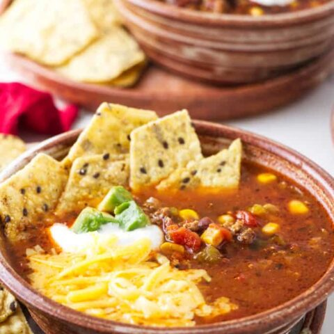 A bowl of taco soup with toppings.