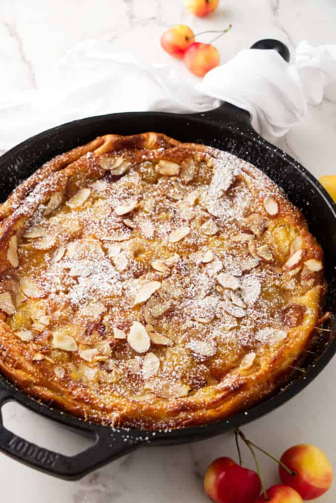 A cherry clafoutis baked in a cast iron skillet.