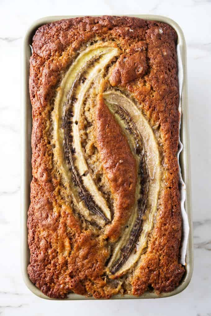 Sourdough banana bread baked in a loaf pan with two halves of bananas on top.