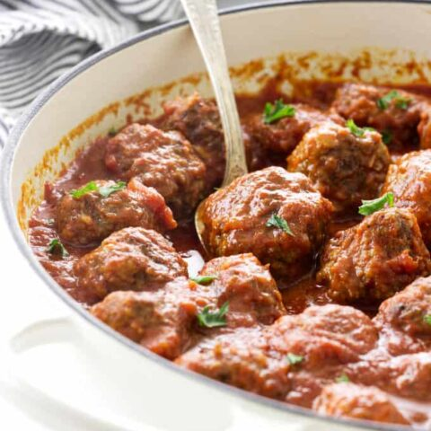 Beef and sausage meatballs in a skillet.