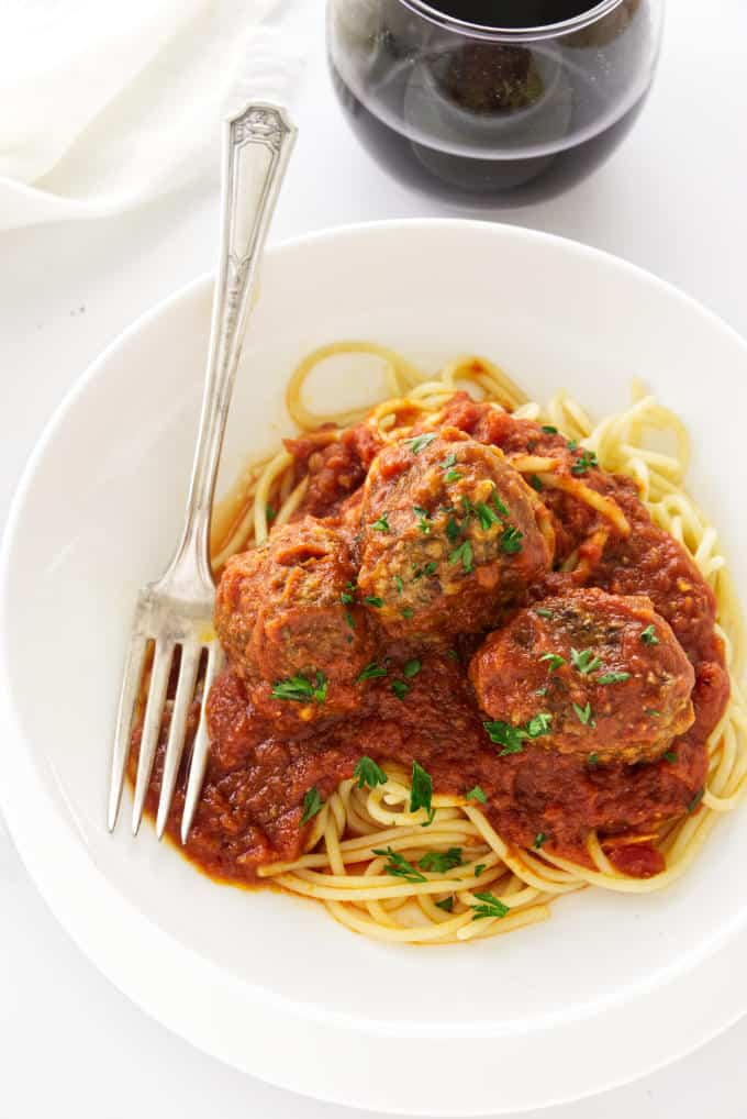 A pasta bowl with pasta and meatballs.