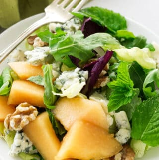 A serving of cantaloupe blue cheese salad with fresh mint leaves.