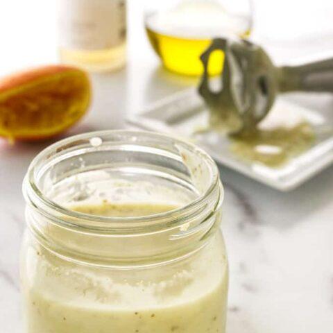 close view of a jar of salad dressing, 1/2 orange, stick blender and ingredients in background