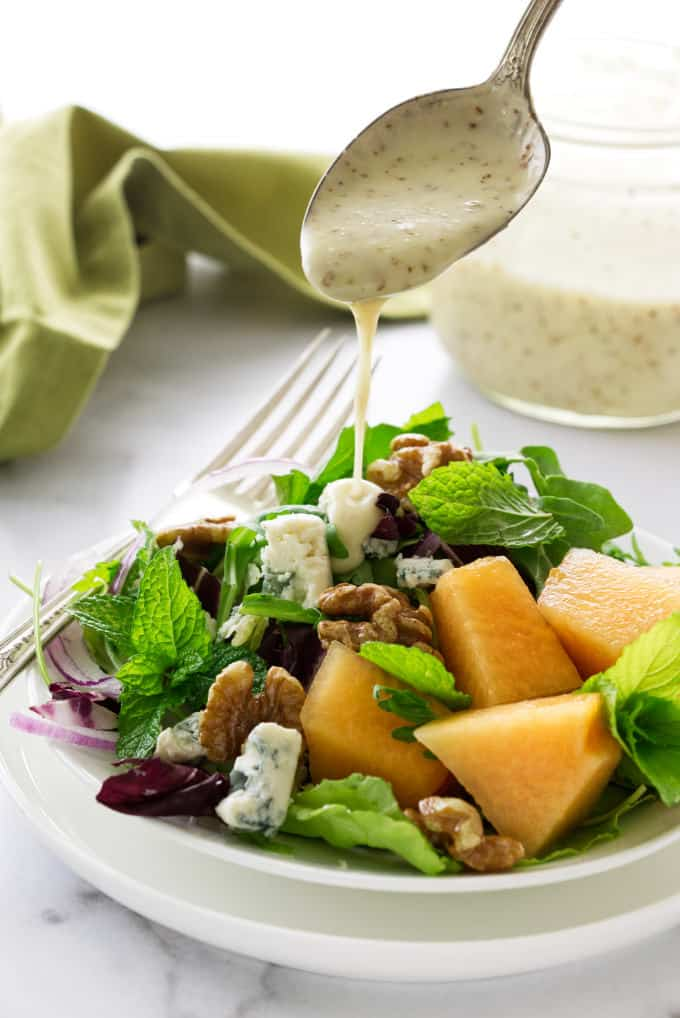 Salad with creamy orange champagne dressing being spooned on