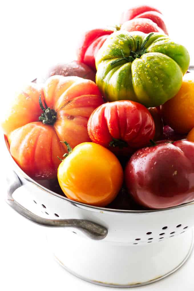 Colander heaped with heirloom tomatoes